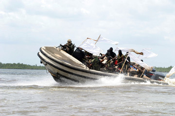 Ethnic militants ride in a speedboat in the Niger delta region of Nigeria