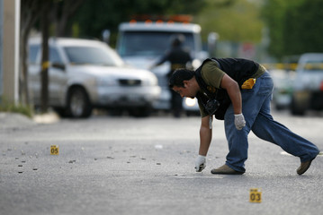 A member of the investigative police force collects bullet casings at the site of a shooting in a wealthy neighbourhood in Monterrey