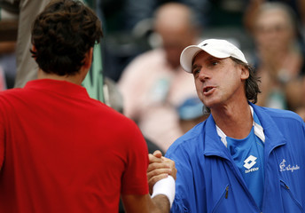 Federer of Switzerland shakes hands with Barazzutti coach of Italy team after winning his Davis Cup world group play-off tennis match against Bolelli in Genoa