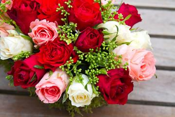 Rosengesteck mit roten, rosafarbenen und weißen Rosen auf einem Holztisch