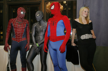 Three people dressed as Spiderman and a girl dressed as Catwoman wait for judging during the costume contest at the Big Apple Comic Convention, in New York