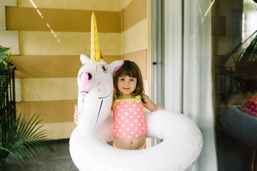 Girl standing with uniorn pool inflatable