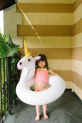 Girl standing with unicorn pool inflatable