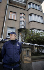 Belgian police officer stands outside house where five dead children have been found in Nivelles