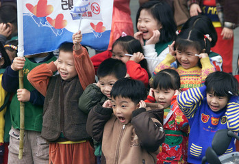 KINDERGARTEN KIDS REACT TO FIRECRACKERS DURING A RALLY IN TAIPEI.
