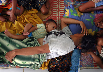 Martina feeds her four-month-old daughter Tali while taking refuge in a church in Dili