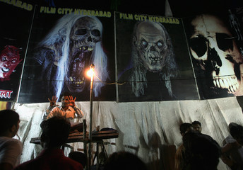 Ticket-seller gestures at entrance gate to horror show at fair in Mumbai