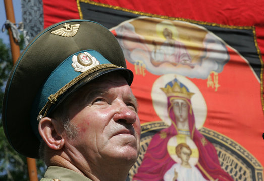 A man wearing a Soviet military hat stands in front of a flag showing an Orthodox icon during a rally denouncing a planned parade by gay activists in Moscow