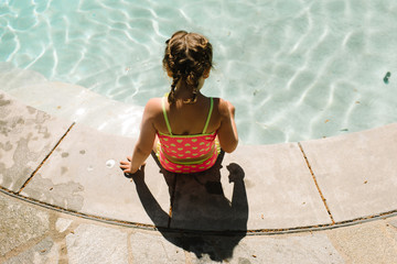 Girl sitting on edge of swimming pool