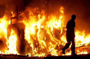 A man walks past a burning vehicle in a Loyalist area in North Belfast.