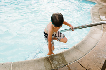 Boy climbing out of swimming pool