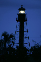 Historic Sanibel Island lighthouse shines at dusk under overcast skies in Sanibel Island, Florida