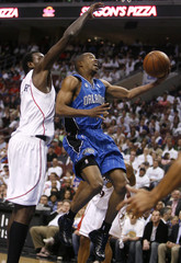 Magic guard Alston shoots under pressure from the 76ers center Dalembert during the first quarter of Game 3 of their NBA Eastern Conference playoff series in Philadelphia