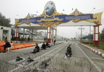 Policemen with riot gear keep guard near anti-government demonstrators outside Hat Yai airport