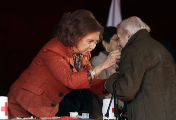 Spain's Queen Sofia places a sticker on a donor's coat in Madrid