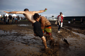 Concert goers play in the mud during the All Points West music festival at Liberty State Park in Jersey City, New Jersey