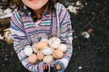Girl holding basket of eggs
