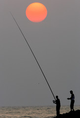 Fishermen drop their line at sunset in Beirut
