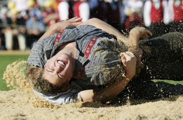 Swiss Alpine wrestlers Bieri and Studer fight in a ring covered with sawdust during the Federal Alpine Wrestling Festival in Aarau