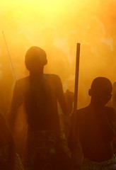 Senegalese youths are silhouetted against dust kicked up during traditional dance in the Casamance region
