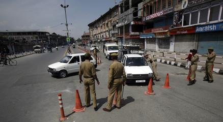 Indian policemen stop traffic at security barricade in Srinagar