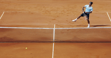 Federer of Switzerland returns a shot to Gremelmayr of Germany during their semi-final match at the Estoril Open tennis tournament in Lisbon