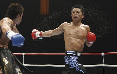 Hiroki Shishido of Japan swings at Keiji Ozaki at K-1 Tournament in Tokyo