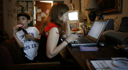 Elvira Arellano uses a computer as her son Saul watches cartoons in their apartment inside Adalberto United Methodist Church in Chicago