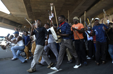 Inkatha Freedom Party supporters wave weapons during a protest against name changes to streets in Durban
