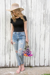 teen girl in frayed blue jeans with daisy bouquet by whitewashed barn