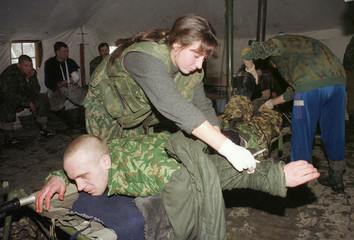 A NURSE PROVIDES AID TO A WOUNDED SOLDIER IN A HOSPITAL OUTSIDE GROZNY.
