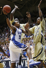 Duke University's Gerald Henderson goes to the basket against Georgia Tech University's Zack Peacock and Alade Aminu in Durham