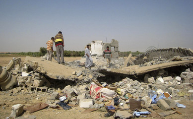 Residents stand on the rubble of a destroyed house after a U.S. air strike in a village near Tikrit