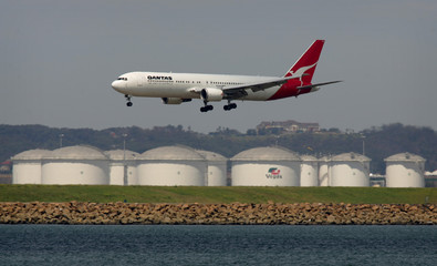 A Qantas passenger plane lands at Sydney airport on a runway in front of an oil refinery.