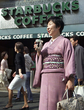 JAPANESE KIMONO-CLAD WOMAN SIPS ON ICED COFFEE OUTSIDE STARBUCKS COFFEE SHOP IN TOKYO.