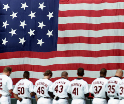 ORIOLES STAND FOR NATIONAL ANTHEM WITH AMERICAN FLAG IN BACKGROUND.