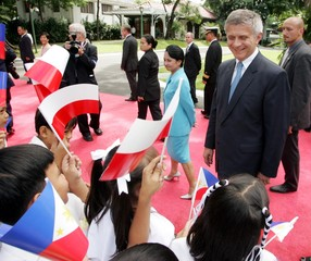 Filipino children wave Polish and Philippine flags during the welcoming ceremony for visiting ...