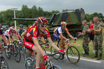THE PACK RIDES PAST MILITARY VEHICLE DURING THIRD STAGE OF TOUR DEFRANCE CYCLING RACE.