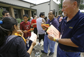 FEMA officials Mohammad Shafique and Bill Willis hand out disaster relief information paperwork to people who have been waiting for hours for food to arrive at a POD or point of distribution center near downtown Houston