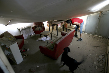 A victim of an earthquake inspects inside a damaged house in a shantytown in Tocopilla