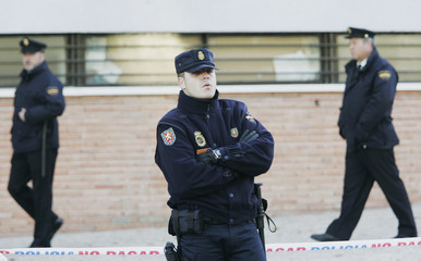 Police officers stand guard at an annex of the High Court in Madrid