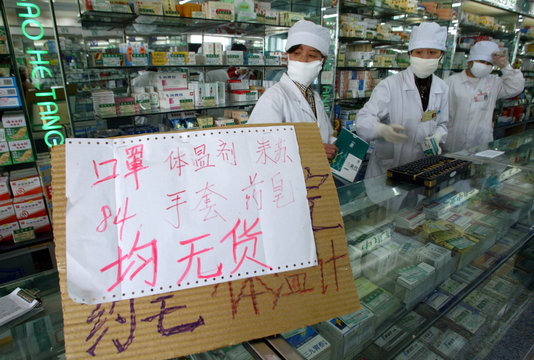 """PHARMACISTS IN BEIJING STAND NEXT TO A SIGN WHICH READS """"MASKS, GLOVES,DISINFECTANT AND THERMOMETERS ..."""