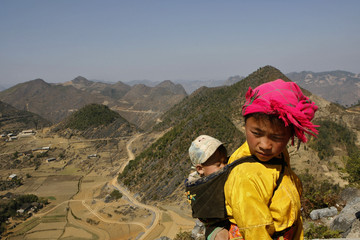 A Vietnamese ethnic Hmong girl carries her sister in Lung Cu village, the border with China