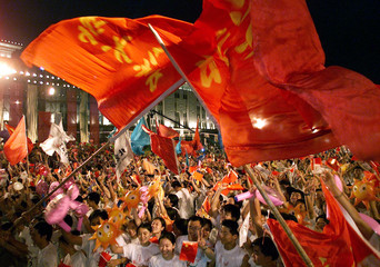 Chinese students at the Millennium Monument in Beijing celebrate after the capital city won the bid ..