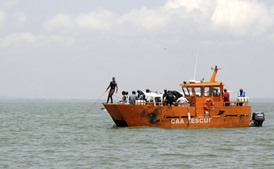 Ugandan civil aviation officials and divers search for the cargo aircraft that crashed into Lake Victoria shortly after taking off from Entebbe international airport Uganda