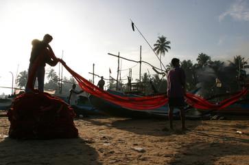 Sri Lankan fishermen unfurl a fishing net in tsunami-hit Dodanduwa fishing village in southern ...