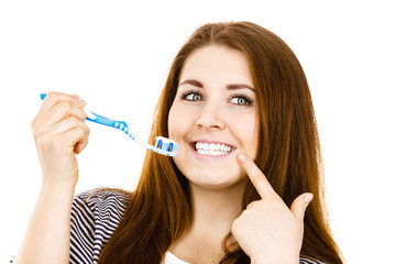 Woman holds toothbrush with paste.