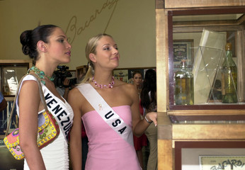 MISS USA AND MISS VENEZUEALA TAKE A LOOK AT ITEMS IN THE BACARDI MUSEUM.