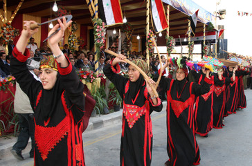 Syrian women in folkloric dresses take part in a show for the opening of Hama city's twelfth Spring Festival