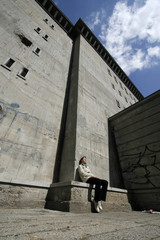 A woman sits outside a former World War Two bunker in Berlin